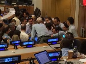 Negotiators huddle to discuss team tactics. It's all action!